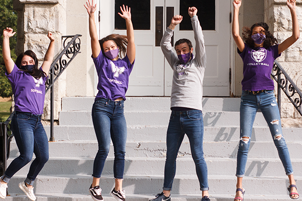 Iowa Wesleyan students jumping in the air